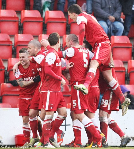 Leaders beaten: Martin Rowlands is mobbed by his Orient teammates after scoring the winner against Tranmere
