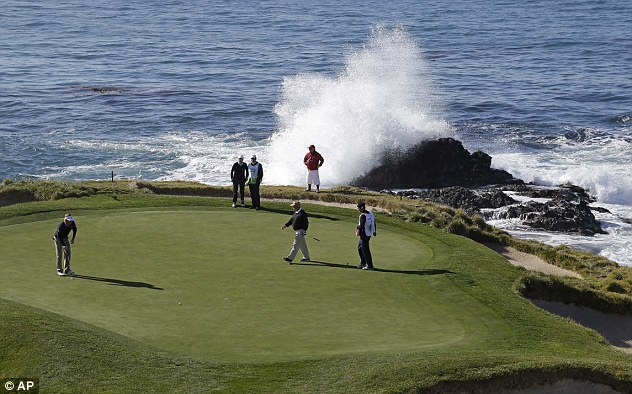 On the rocks: A wave breaks behind Snedeker as he goes for glory