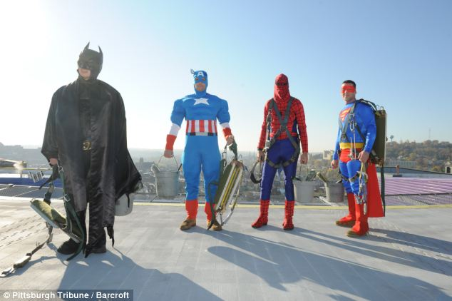 The high-rise window washers put their safety harnesses around the costumes before unfurling ropes from the 12th floor