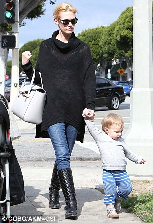 Look mommy, I'm walking: January holds her son's hand protectively as he takes some tentative steps