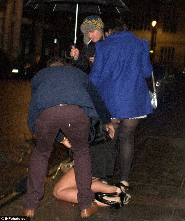 Raining champion: Kierston sat on the floor briefly while a gentleman held an umbrella over her