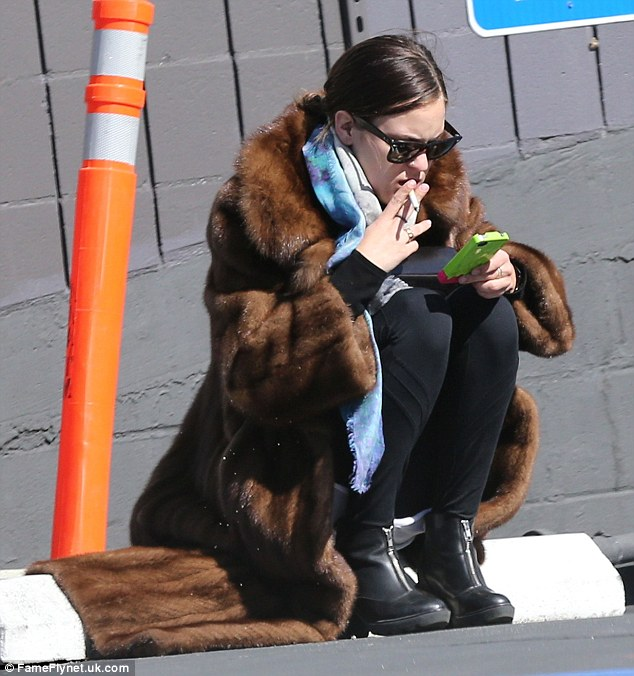 What a drag: Tallulah Willis puffed away on a cigarette in a long fur coat while squatting in a car-park in West Hollywood Monday