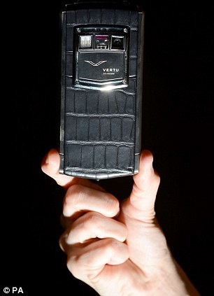 A man holds a Titanium Black Alligator Vertu Ti smartphone