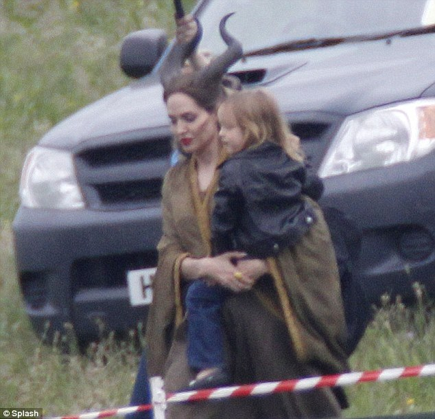 Fantasy film: Angelina carrying Vivienne's twin brother Knox on set of Maleficent last year