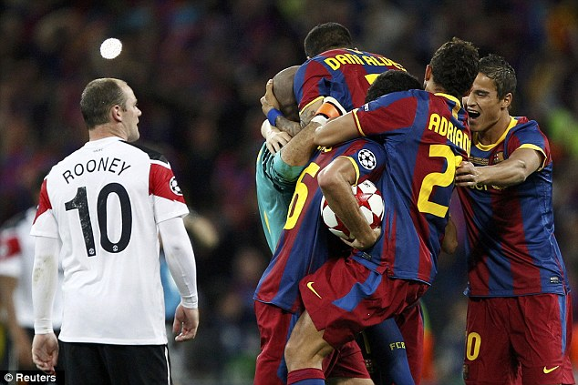 Outclassed: Wayne Rooney (left) watches the Barcelona players celebrate after the Champions League final in 2011