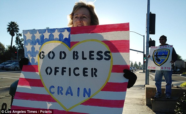 Blessings: Ann Nunez and David Nunez of Riverside wait the corner of Cannon rd and Allesandro blvd, waiting for the funeral procession for slain Riverside Police officer Michael Crain