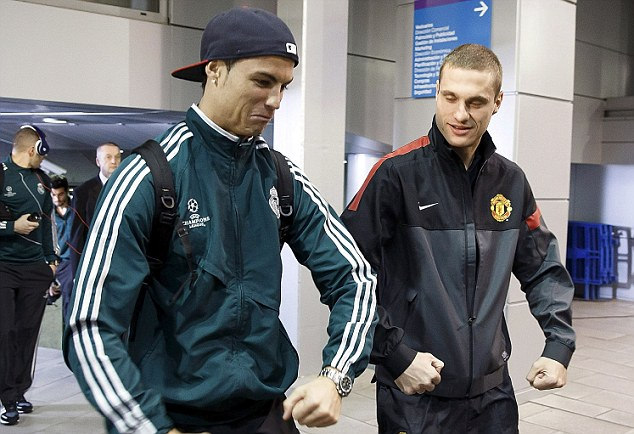 Old friends: Nemanja Vidic arriving at the Bernabeu with former team-mate Cristiano Ronaldo ahead of tonight's match