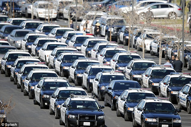 Convoy: Funeral cortege for Officer Michael Crain arrives at the Riverside Community Church, in California. Security was tight with rooftop snipers and armored police vehicles standing guard