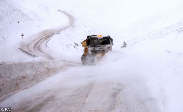 Warning: The Met Office has issued severe weather warnings for much of Scotland and northern England for today. In this picture a gritter is busy clearing the road after heavy snowfall near Tomintoul in Scotland this morning