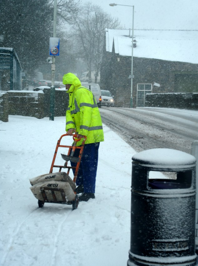 A man pulls grit along on a trolley in Ramsbottom in Bury, Greater Manchester