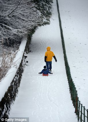 Fun for some: A man pulls a boy on a sledge in Blanefield, Scotland, (left)
