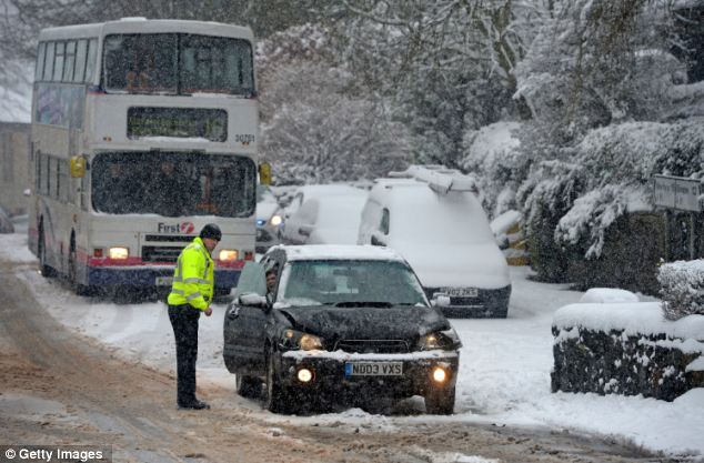 No way through: A police officer issues advice to a motorist on a snow-covered road in Blanefield, Scotland today