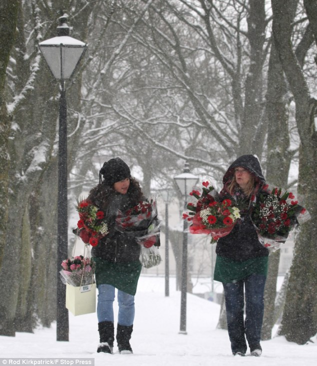 Unable to use their delivery van, florists Margaret Knowles and Claire Foster brave a blizzard in Buxton, Derbyshire, to deliver Valentine blooms