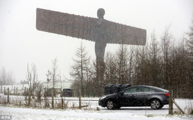 The famous Antony Gormley sculpture stares out over the snowy landscape this afternoon