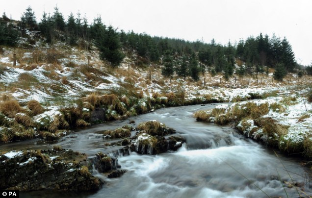 A stream runs down between snow-dusted hills outside Aberystwyth, Wales