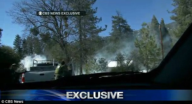 Shootout: Sheriff's deputies can be seen firing shots near the cabin, as it begins to burn
