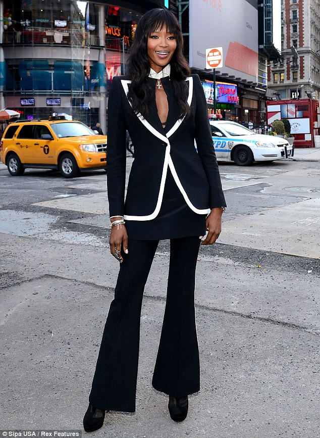 Racy lady: Naomi displayed her black bra under her matching black suit, which featured white trim on the jacket and trousers