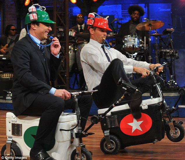 On your marks: The actor and talk show host were both sporting novelty beer hats as they zipped about on motorised coolers