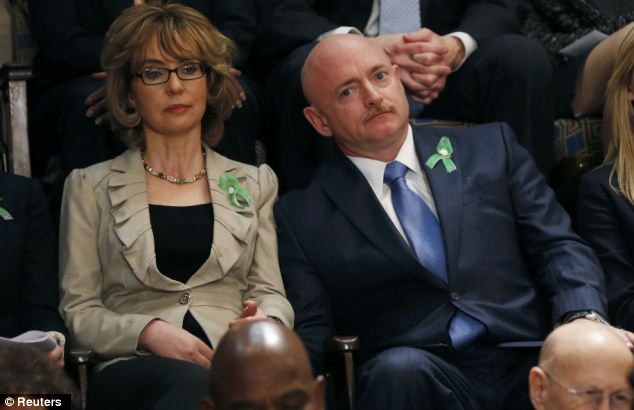 Gabby Giffords, pictured with her husband Mark Kelly, wore green ribbons in memory of the victims of Sandy Hook as they listened to President Obama's State of the Union speech