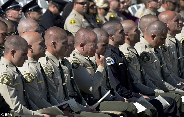 Uniform: Riverside County Sheriffs deputies sit in the front row of the overflow seating area outside the funeral for Riverside Police Department Office Michael Crain