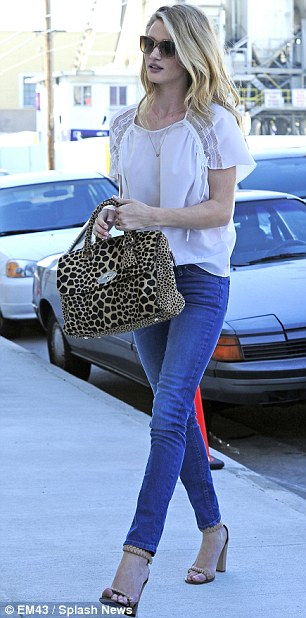 Pretty and polished: The 25-year-old British beauty paired straight-leg denim with nude heels, a white blouse and animal print handbag