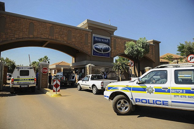 Police: South African police vehicles enter the Siverwoods security estate in Pretoria East where famous South African paralympic and Olympic sprinter, Oscar Pistorius