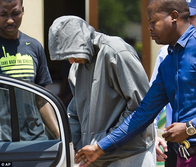 Charged: Oscar Pistorius leaves the Boschkop police station in Pretoria before going to court