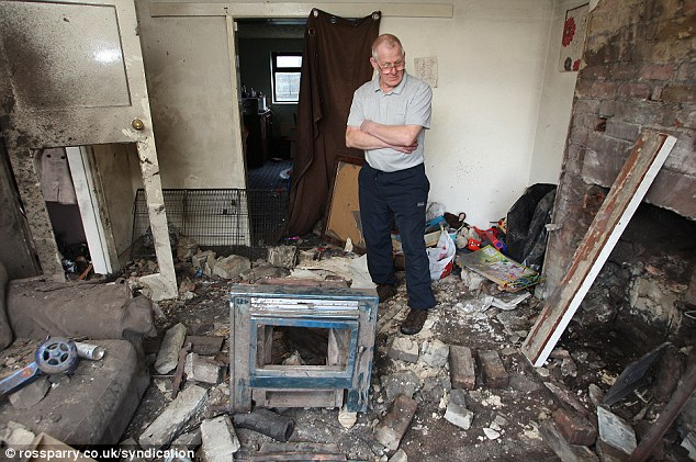 Destruction: Amy Rooke's father Dave inspects lounge in his daughter's house after a wood burning stove exploded tearing the room to bits