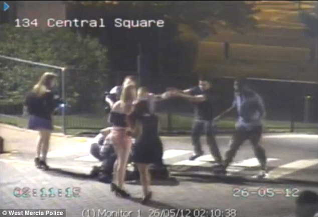 Two men grapple on the floor as women in mini-skirts and high heels watch on