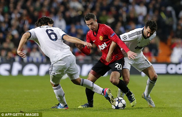 No way through: Robin van Persie was well shackled on Wednesday night, with Sami Khedira sticking the boot in here
