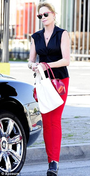 Lady in red: Melanie Griffith showed she was in the spirit wearing red pants, glasses and handbag in Los Angles, California. Strangely she changed shoes midway through shopping
