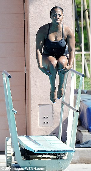Take off: Keshia looked athletic in her black swimsuit as she launched high and jumped into the pool