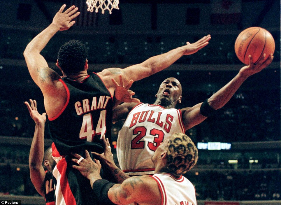 Heroics: Jordan made the No 23 his own during his spells at the Chicago Bulls. Here, he battles with Portland Trailblazers' Brian Grant under the net