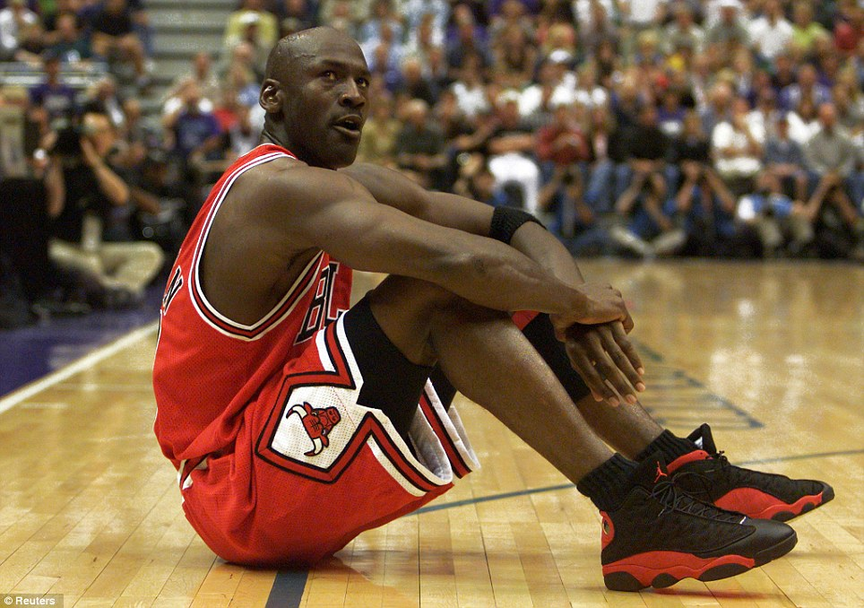 Champion: In this picture, Jordan sits on the floor between plays as his Chicago Bulls team trail the Utah Jazz in June 1998