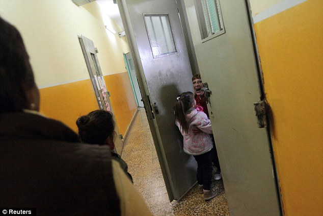 Happy reunion: Prisoner Valeria Cigara, 28, right, hugs her four-year-old daughter Milagros during their visit
