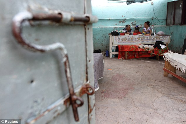 Lunch: Prisoner Silvia Rodas, right, has lunch with her daughter Anahi, 9, and her father Carlos, during a visit to the prison