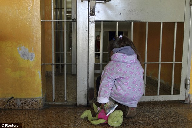 Sad life: Four-year-old Milagros, pictured, peers at her mother Valeria Cigara, 28, who is currently in prison awaiting trial for robbery, in Magdalena August 19, 2012