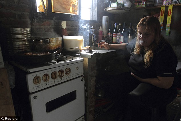 Kiosk life: Julia Romero, 42, who is under house arrest to serve the last 11 years of an 18-year sentence for homicide, smokes inside her home in Buenos Aires August 10, 2012