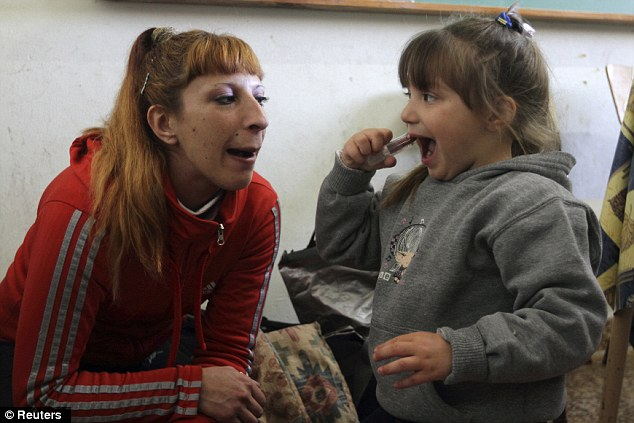 Playing around: Four-year-old Milagros puts on lipstick while her mother Valeria Cigara, 28, watches