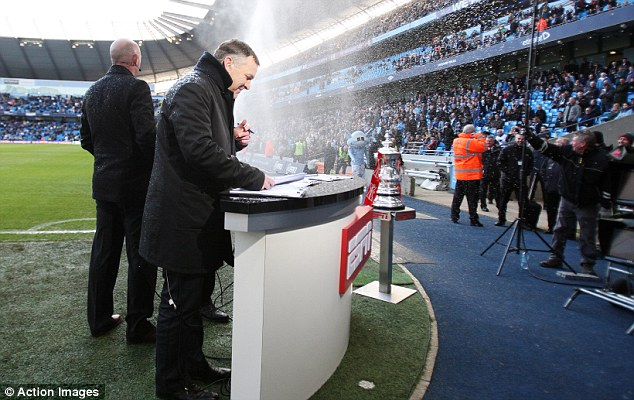 Didn't see that coming: ESPN presenter Ray Stubbs is sprayed by the sprinklers before the game between Manchester City and Leeds United at the Etihad Stadium