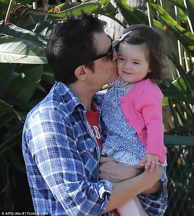 Affectionate: Johnny plants a big kiss on Arlo's cheek as he holds her close