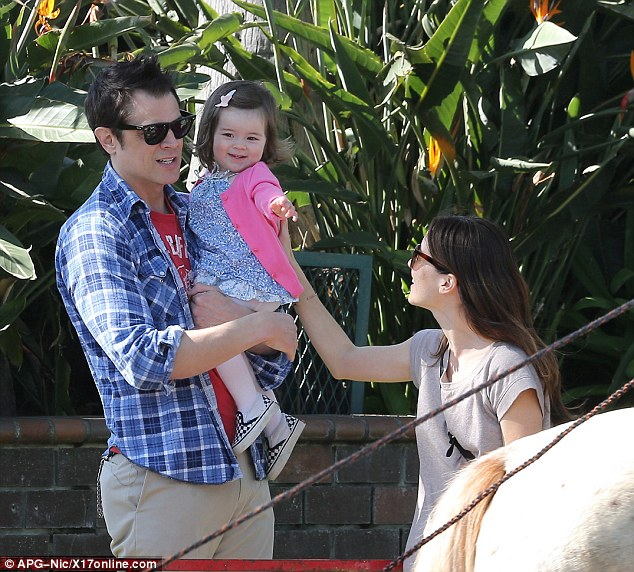 Loving mom: Naomi beamed as she placed a hand on her daughter's back as the little girl pointed excitedly at the ponies