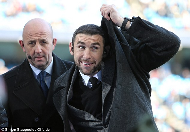 Take cover: Martin Keown shelters himself from the water from the pre-match sprinklers