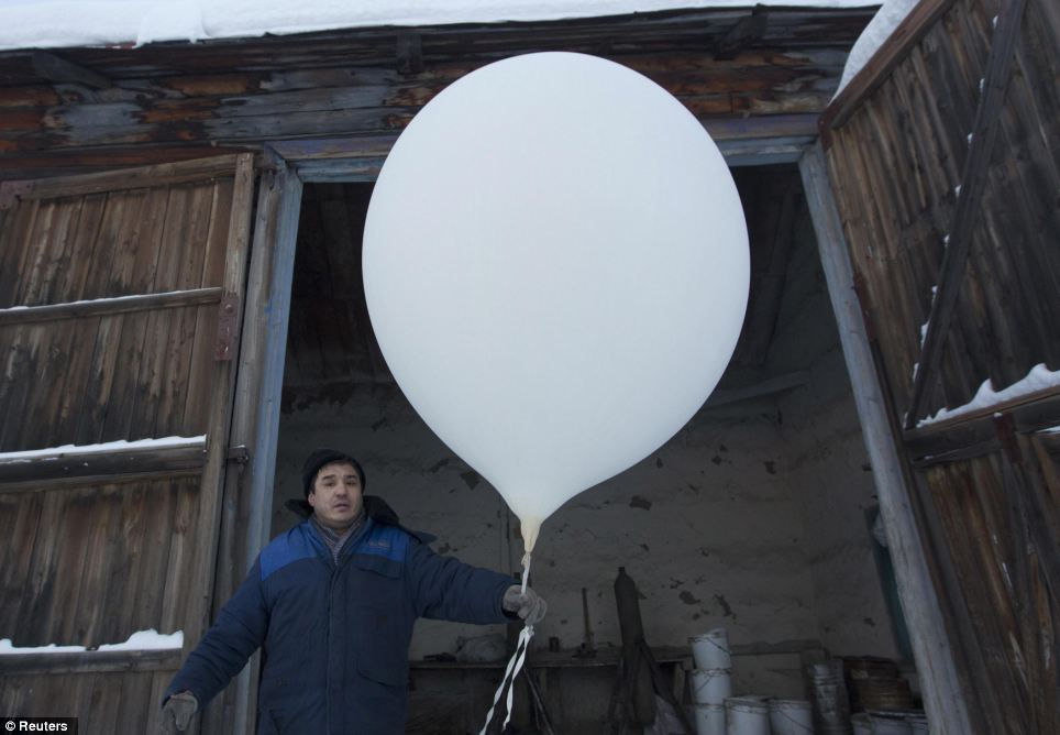 Wintry weather: Meteorologist Sergei Burtsev, 41, prepares to launch a weather balloon to record the temperatures where the length of a day varies from 3 hours in December to 21 hours in the summer