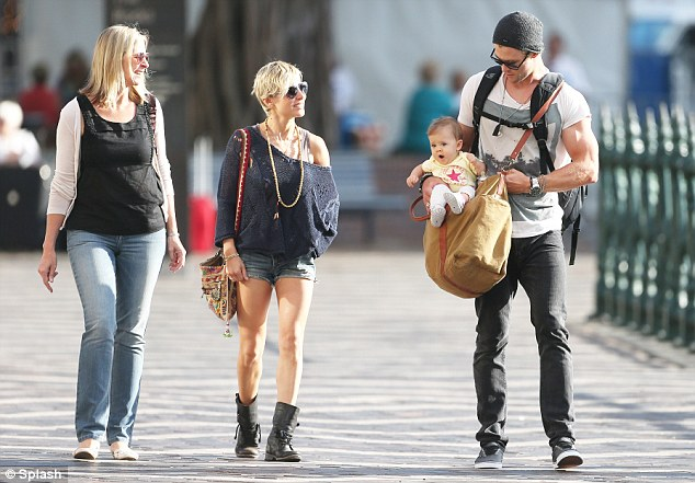 Flex some muscle: The action star showed off his rippling biceps as he enjoyed the sunny afternoon with his young family