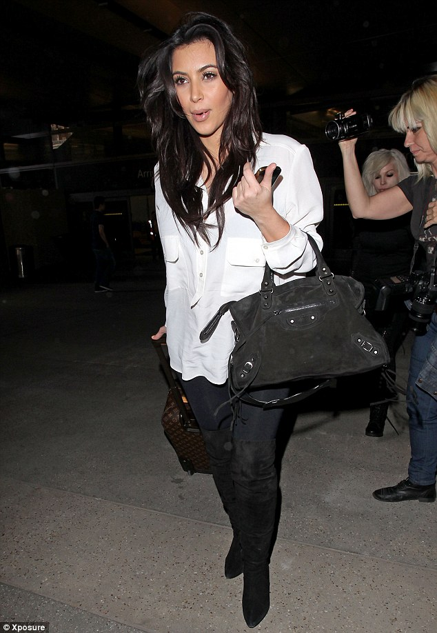 Ready for bed: Kim Kardashian arrives home from Nigeria looking tired after her brief stay in the African country on Monday