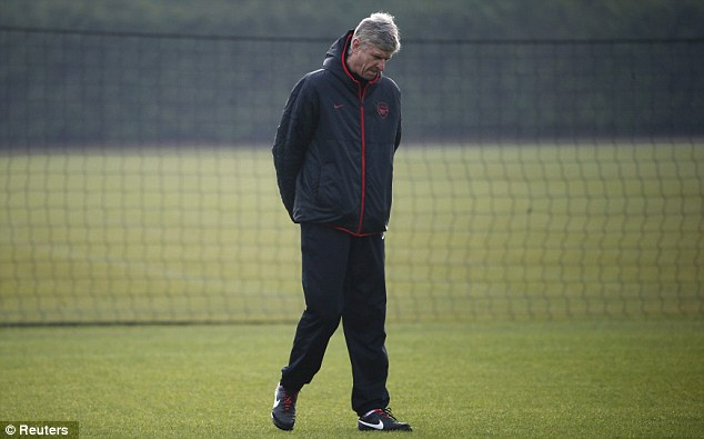 Plenty to ponder: Wenger cuts a lonely figure during Arsenal's training session on Monday