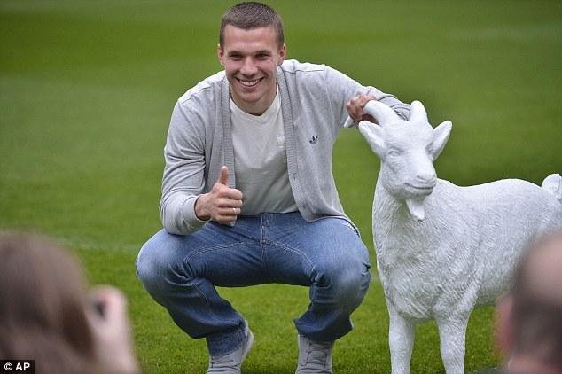 Home: Podolski poses with the FC Cologne mascot