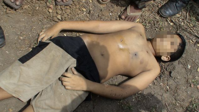 A picture taken hours later shows the boy lying dead on the ground with up to five bullet wounds to his chest
