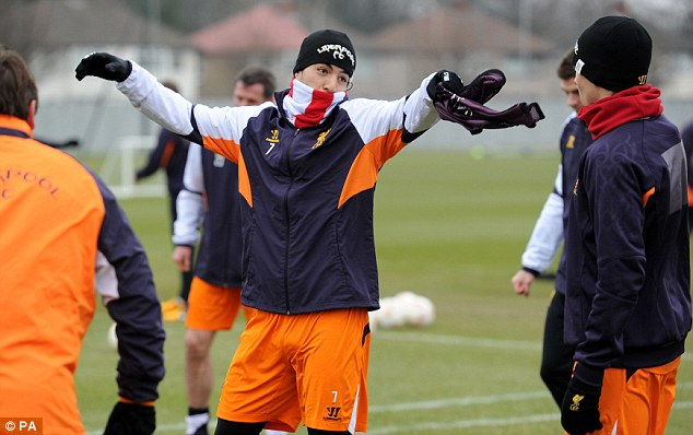 Scarf ace: Luis Suarez wraps up as Liverpool train ahead of entertaining Zenit at Anfield on Thursday